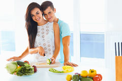 Couple cooking healthy food and smiling at the camera. Lifestyle Stock Photos