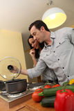 Couple cooking in a kitchen Stock Photography