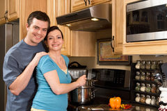 A Couple Cooking in The Kitchen - Horizontal. A loving couple standing in the kitchen cooking together.  Horizontally framed shot with both people looking at the Stock Photos