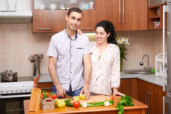 Couple cooking in kitchen interior with fresh fruits and vegetables, healthy food concept, pregnant woman and man Stock Images