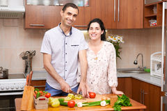 Couple cooking in kitchen interior with fresh fruits and vegetables, healthy food concept, pregnant woman and man Stock Photos