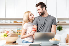 Couple cooking in kitchen with laptop computer Royalty Free Stock Photos