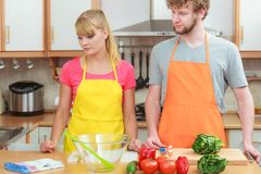 Couple cooking in kitchen reading cookbook. Happy young couple having fun in modern kitchen at home preparing fresh vegetables food reading cookbook looking for Stock Photos