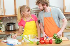 Couple cooking in kitchen reading cookbook. Happy young couple having fun in modern kitchen at home preparing fresh vegetables food reading cookbook looking for Royalty Free Stock Photo