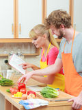 Couple cooking in kitchen reading cookbook. Happy young couple having fun in modern kitchen at home preparing fresh vegetables food reading cookbook looking for Stock Photo
