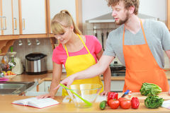 Couple cooking in kitchen reading cookbook. Happy young couple having fun in modern kitchen at home preparing fresh vegetables food reading cookbook looking for Stock Images