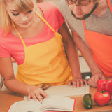 Couple cooking in kitchen reading cookbook Stock Photo