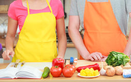 Couple cooking in kitchen reading cookbook. Happy young couple having fun in modern kitchen at home preparing fresh vegetables food reading cookbook looking for Royalty Free Stock Photography