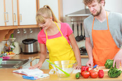 Couple cooking in kitchen reading cookbook Stock Images