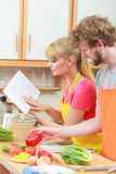 Couple cooking in kitchen reading cookbook. Happy young couple having fun in modern kitchen at home preparing fresh vegetables food reading cookbook looking for Royalty Free Stock Images