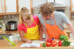 Couple cooking in kitchen reading cookbook. Happy young couple having fun in modern kitchen at home preparing fresh vegetables food reading cookbook looking for Stock Photography