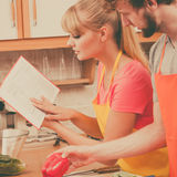 Couple cooking in kitchen reading cookbook. Happy young couple having fun in modern kitchen at home preparing fresh vegetables food reading cookbook looking for Stock Image