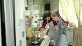 Couple cooking and laughing. Clumsy people in the kitchen. Keep having fun stock video footage