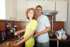 Couple  cooking meat. In her kitchen Royalty Free Stock Images