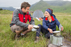 Couple cooking outside on camping trip and smiling Royalty Free Stock Photos