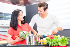 Couple cooking pasta in domestic kitchen Stock Photography