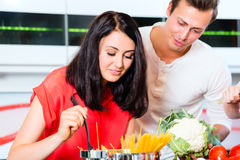 Couple cooking pasta in domestic kitchen Royalty Free Stock Photo