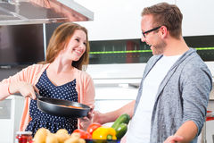 Couple cooking pasta in kitchen Royalty Free Stock Photography