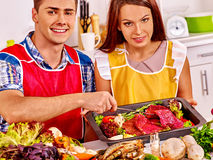 Couple cooking raw meat dinner at kitchen Royalty Free Stock Photography