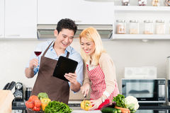 Couple cooking after recipes from tablet computer Royalty Free Stock Image