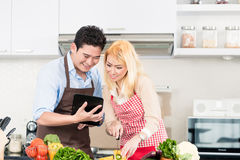 Couple cooking after recipes from tablet computer Royalty Free Stock Photos