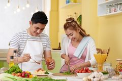 Couple cooking spaghetti and salad royalty free stock photos