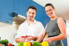 Couple cooking together in kitchen Royalty Free Stock Images