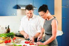 Couple cooking together in kitchen Stock Images