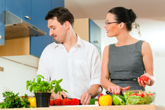 Couple cooking together in kitchen Royalty Free Stock Photos