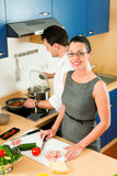 Couple cooking together in kitchen. Young couple - men and women - cooking in their kitchen at home preparing vegetables for salad and pasta sauce Royalty Free Stock Images