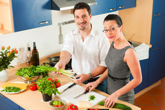 Couple cooking together in kitchen. Man and woman in the kitchen - they preparing the vegetables and salad for dinner or lunch Royalty Free Stock Photos