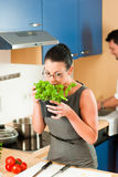 Couple cooking together in kitchen. Man and woman in the kitchen - they preparing the vegetables and salad for dinner or lunch Stock Image