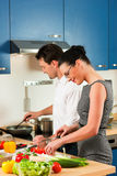 Couple cooking together in kitchen. Man and woman in the kitchen - they preparing the vegetables and salad for dinner or lunch Stock Photography