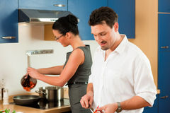 Couple cooking together in kitchen. Man and women in the kitchen - they preparing the vegetables and salad for dinner or lunch Stock Photo