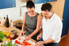 Couple cooking together in kitchen. Man and women in the kitchen - they preparing the vegetables and salad for dinner or lunch Royalty Free Stock Photography