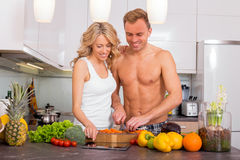 Couple cooking together in kitchen and using tablet Stock Images