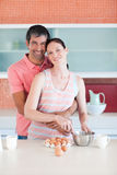 Couple cooking together looking to the camera Stock Photos