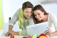 Couple cooking and using tablet Royalty Free Stock Photo