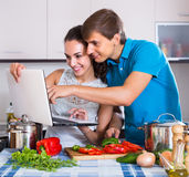 Couple cooking vegetables with laptop Royalty Free Stock Photography