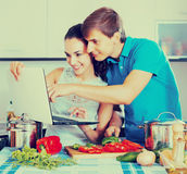 Couple cooking vegetables with laptop Stock Photography