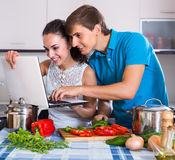 Couple cooking vegetables with laptop Stock Image