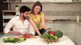 Couple Cooks Healthy Meal. Happy young couple cooking healthy meal, using silver tablet while cooking, warm atmosphere in cozy kitchen, healthy lifestyle stock video