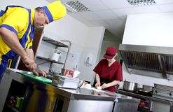 Couple of cooks in a restaurant kitchen. Couple of cooks in action in a restaurant kitchen royalty free stock photos