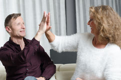 Couple on couch with high five Stock Images