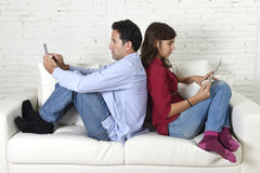 Couple on couch ignoring each other using mobile phone and digital tablet in internet addiction Stock Photos