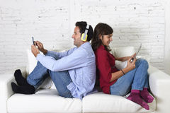 Couple on couch ignoring each other using mobile phone and digital tablet in internet addiction. Young attractive couple sitting on home couch together back to royalty free stock photos