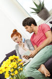 Couple at the Couch with Laptop, Card and Money Stock Photography