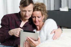 Couple on couch looking on tablet Stock Images