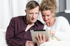 Couple on couch looking on tablet Royalty Free Stock Images