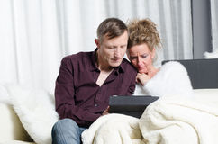 Couple on couch looking on tablet Stock Image